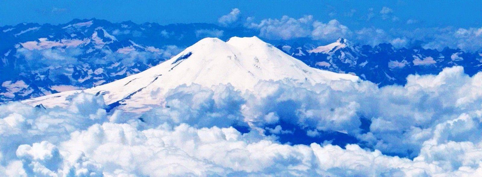 Эльбрус — именно таким он встретил нас наверху, выше облаков, в тот сентябрьский день 1998 года в Карачаево-Черкессии, когда мы с борта маленького вертолёта старались снять эту гордость народов Кавказа со всех сторон. Внизу, под облаками, тогда была жара - выше 30 градусов, а тут, на борту при открытых дверях, наша команда быстро замёрзла напрочь…